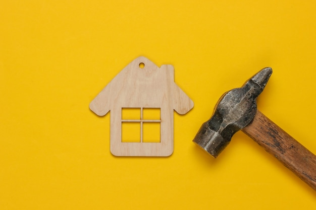 How to build a house? diy concept. hammer and mini house figurine on yellow background