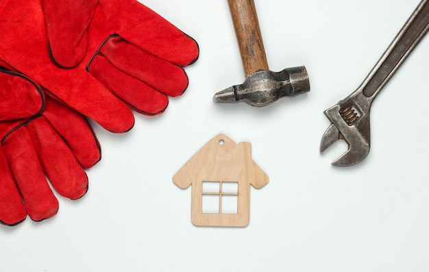 How to build a house? diy working tools and mini house figurine on a white background