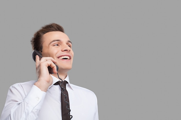 어떻게 도와 드릴까요? 셔츠에 넥타이를 매고 전화 통화를 하고 회색 배경에 서서 웃고 있는 쾌활한 청년