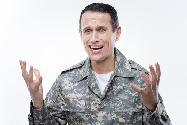 Почему. безрадостный красивый военный мужчина смотрит перед собой и думает о том, что делать, будучи в растерянности