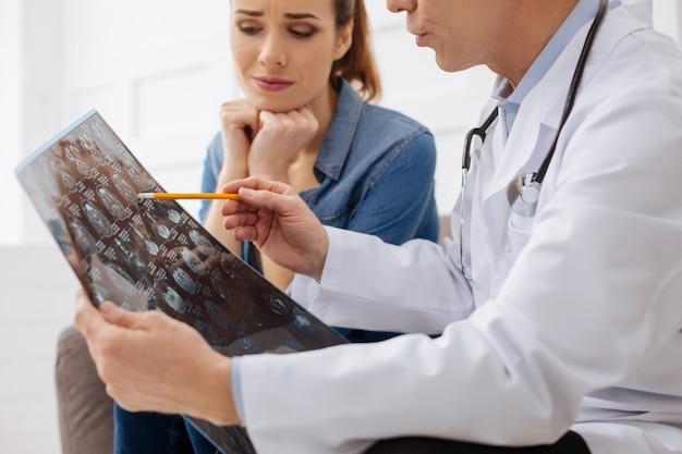 どうしてそれが起こるのでしょうか。彼女のセラピストが彼女の診断を説明し、x線を指している間心配そうに見える心配している患者に焦点を合わせた女性