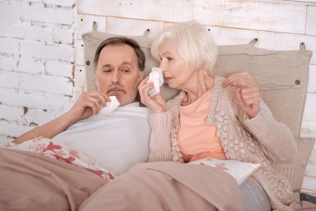 우리가 어떻게. 매우 아픈 노인 부부는 침대에 누워 담요로 덮여 있고 코를 불고 있습니다.