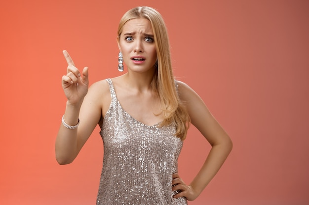 なんてことするんですか。失望した失望した若い女性が尊敬を要求する不平を言って人差し指を叱る指導レッスンを上げることは、不快な赤い背景に悩まされて立っている指示を与えます。