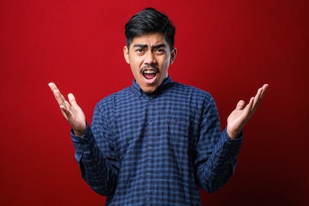 어떻게 할 수 있니? 화가 난 아시아 남성이 손을 들고 서서 이유를 묻는 초상화. 빨간색 배경 위에 촬영된 실내 스튜디오