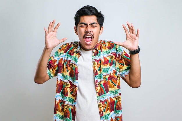 なんてことするんですか?なぜかと尋ねて、手を上げて立っているイライラする欲求不満のアジア人男性の肖像画。白い背景の上に撮影された屋内スタジオ