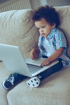 How dad uses this thing? high angle view of little african baby boy using his laptop while sitting on the couch at home