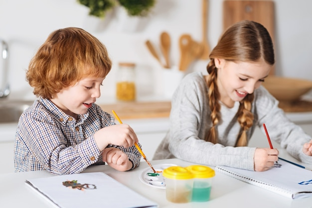 How did you do that. cheerful diligent charming siblings painting funny pictures using watercolors while sitting at the table in a kitchen