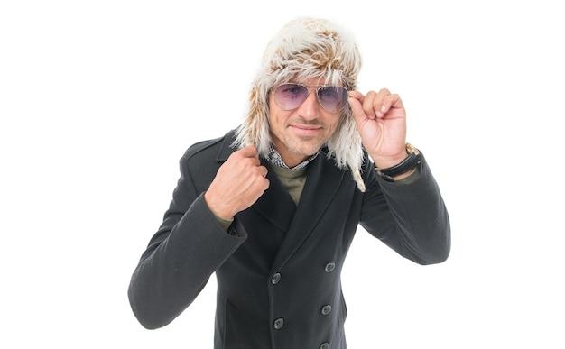 いかがですか。幸せな休日。冬服のひげを生やした男。寒い季節にぴったりのウォームウェア。イヤフラップの帽子をかぶった無精ひげを生やしたハンサムな男。成熟した男は白で隔離された眼鏡を通して見る。天気予報。