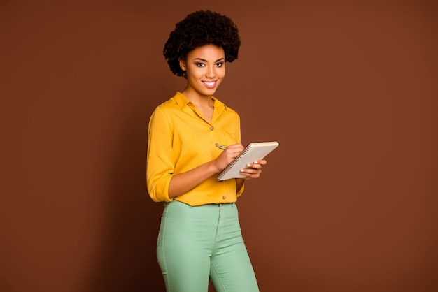 How to get inspiration? photo of beautiful dark skin curly lady author hold diary noting comments writers training wear yellow shirt green trousers isolated brown color