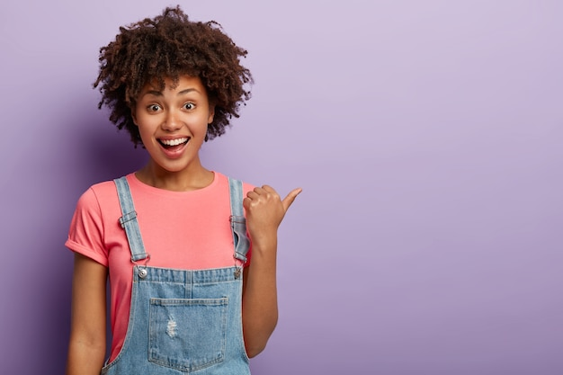 Как интересно! веселая темнокожая молодая женщина указывает большим пальцем на правую сторону