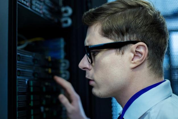 Как интересно. серьезный молодой оператор смотрит на оборудование и думает