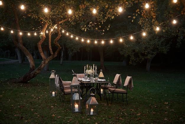 Как богатые люди ужинают. подготовленный стол ждет еду и посетителей. вечернее время