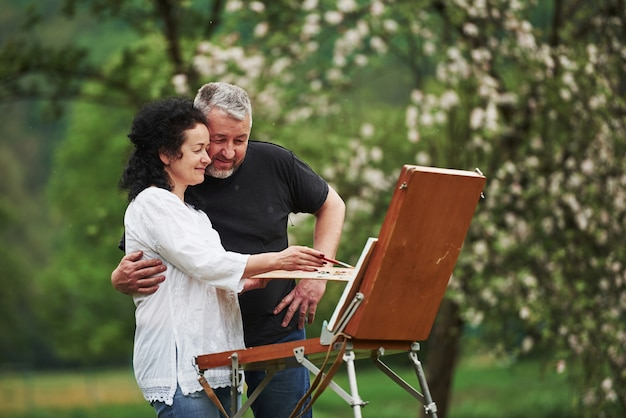 Как вам это выглядит. пожилая пара отдыхает и вместе работает над краской в парке
