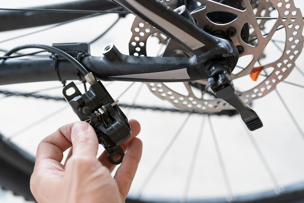 How to maintenance a mtb hydraulic disc brake caliper : repairman holding a hydraulic rear disc brake caliper on a mountain bike.