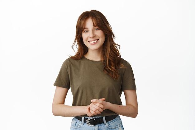 Как я могу помочь вам. улыбающаяся дружелюбная женщина, стоящая в приятной формальной позе, удерживая эмоции вместе, готовая предложить помощь или содействие, стоя на белом.