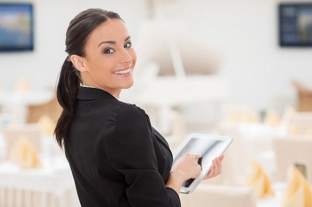 Чем я могу тебе помочь? привлекательная молодая женщина в формальной одежде работает на цифровом планшете и смотрит через плечо, стоя в ресторане