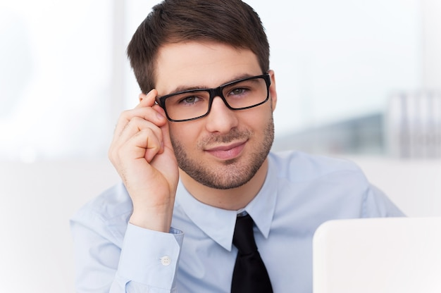 How may i help you? cheerful young man in shirt and tie looking out of the laptop and adjusting his glasses while sitting at his working place