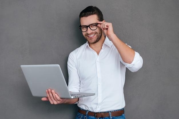 どのように私はあなたを助けることができますか?ノートパソコンを持って笑顔のハンサムな若い男