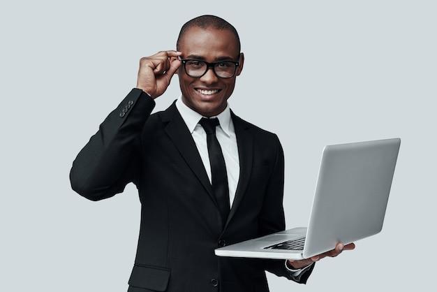 어떻게 도와 드릴까요? 회색 배경에 서서 카메라를 보고 웃고 있는 정장 차림의 젊은 아프리카 남자