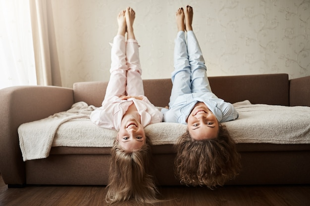 How nice to lie and fool around all day with girlfriend. charming childish european women lying on sofa in nightwear with lifted hands and head upside down, hair touching floor, smiling broadly