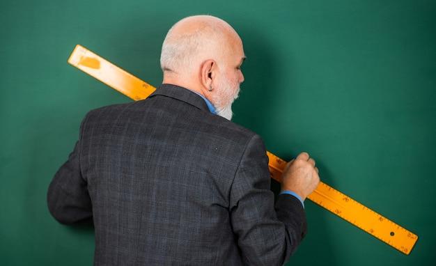 数学でどのように成功するかさまざまな科目や分野を探る男性家庭教師の黒板の背景