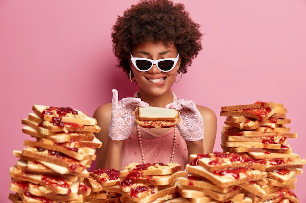 How tasty! pleased afro american lady dressed in fashion clothes, lace gloves, trendy sunglasses, being on banquet, poses near bread toasts, isolated on pink wall, holds appetizing sandwich