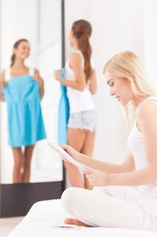 このドレスは私にどのようにフィットしますか?別の女性が前景に座って雑誌を読んでいる間、ドレスを持って鏡を見ている美しい若い女性