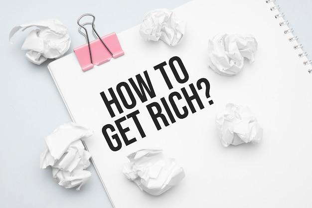 金持ちになる方法。白紙の紙、赤いペーパークリップ、単語のアイデア、しわくちゃの紙の札束