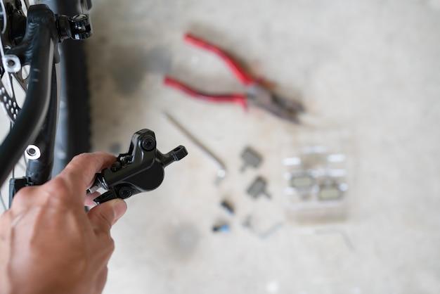 Mtb油圧式ディスクブレーキキャリパーのメンテナンス方法:マウンテンバイクで油圧式リアディスクブレーキキャリパーを保持している修理工。