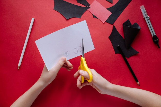 Как сделать летучую мышь из бумаги в домашних условиях. руки делают ремесло из бумаги. пошаговая фото инструкция. шаг 8. вырежьте глаза и клыки. детский diy арт-проект.