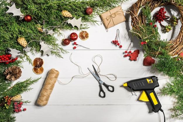 クリスマスのドアリースの作り方。作業プロセス。デコレータの職場。上面図。スペースをコピーします。静物。フラットレイ。