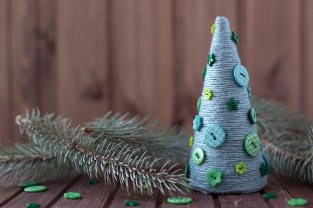 自宅でロープとボタンからクリスマスツリーを作る方法。ステップバイステップの説明。