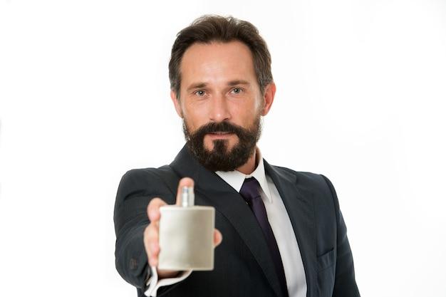 正しい香りの選び方。機会に応じて男性に最適な香水を選択する方法。これはビジネスマンにとって最高の香りです。男ひげを生やしたハンサムなビジネスマンは、焦点がぼけたボトルの香水を保持します。