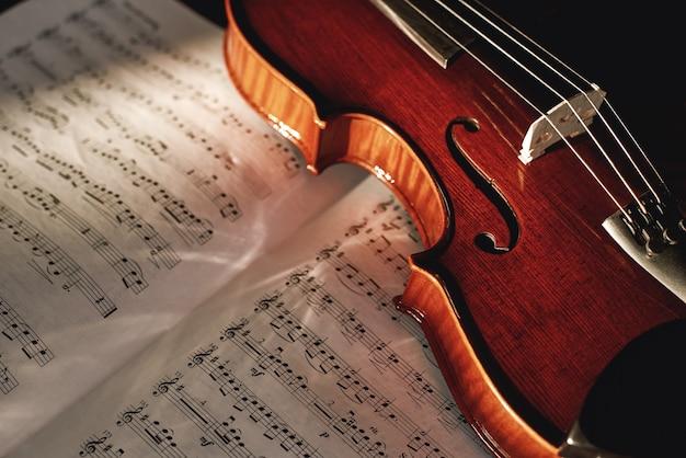 바이올린 음표 읽는 방법 악보와 함께 시트에 누워 있는 갈색 나무 바이올린의 보기를 닫습니다. 악기. 음악 장비. 바이올린 레슨