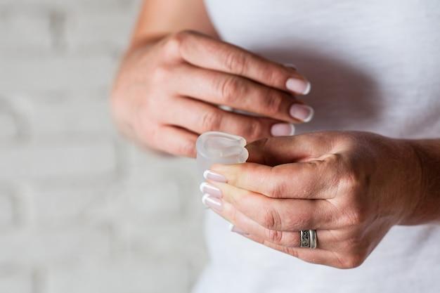 Как пользоваться менструальной чашей в женских руках. женщина держит цветок и силиконовую гигиеническую чашку, новое устройство для минимизации отходов и защиты окружающей среды.
