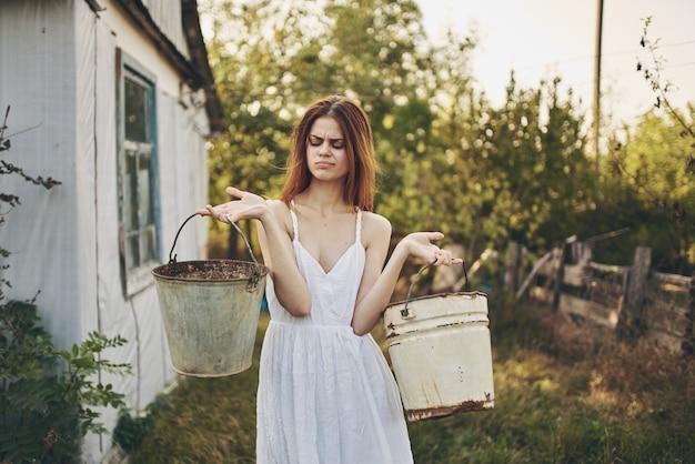 自然農園の村の建物の近くにバケツを持った幸せな女性はどうでしたか。