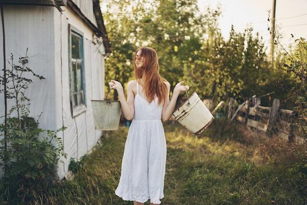 自然農園の村の建物の近くにバケツを持った幸せな女性はどうでしたか
