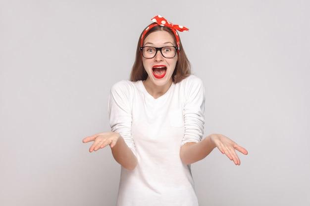 어떻게 했어? 믿을 수 없군. 주근깨, 검은 안경, 빨간 입술, 머리띠가 있는 흰색 티셔츠를 입은 아름다운 감정적 젊은 여성의 초상화. 밝은 회색 배경에 고립 된 실내 촬영.