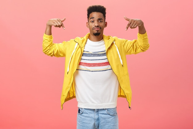 How you like my style. cool and handsome stylish young man with beard in trendy yellow jacket over t-shirt raising hands pointing at himself smirking and raising eyebrow being unsure how he looks. Free Photo