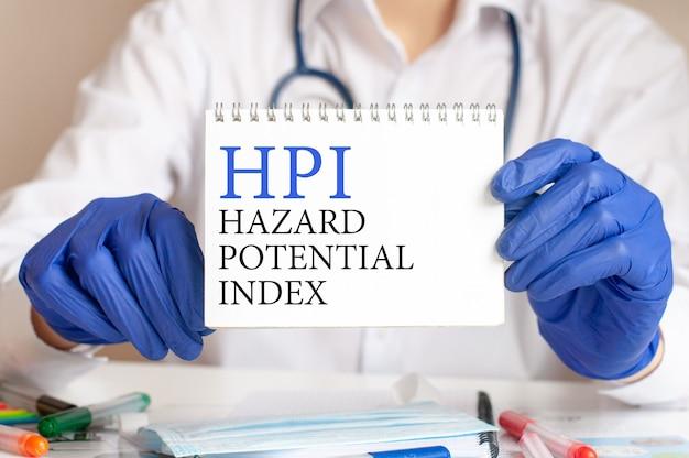 의사의 손에 hpi 카드. 텍스트 hpi-위험 잠재력 지수, 의료 개념에 대한 짧은 종이를 들고 파란색 장갑에 의사의 손.