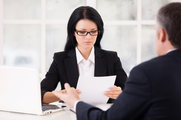 Hr director and job candidate. confident young woman in formalwear holding a paper and looking at it while grey hair man sitting in front of her and gesturing
