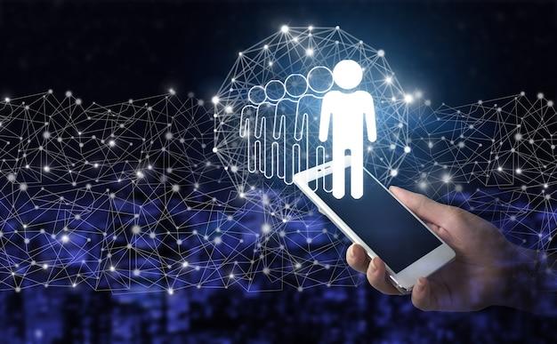 Hr 인사 채용 채용. 디지털 홀로그램 휴먼, 리더 사인이 있는 흰색 스마트폰을 손에 들고 도시의 어두운 배경을 흐리게 표시합니다. 비즈니스 커뮤니케이션 개념입니다. 팀워크.