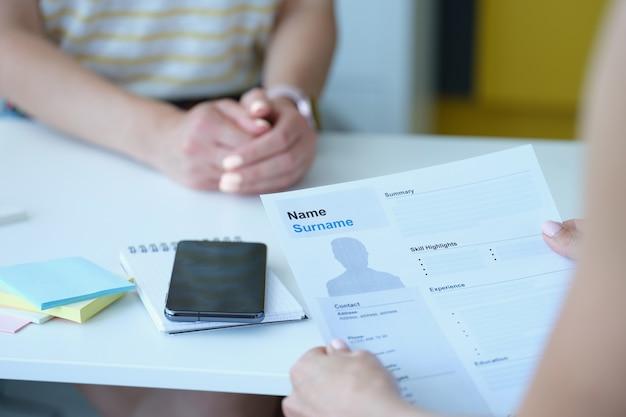 人事マネージャーは職場のクローズアップで履歴書を保持します
