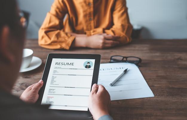 人事マネージャーは、企業としての就職を検討するために、求人応募フォームに履歴書を記入する求職者に面接しています。