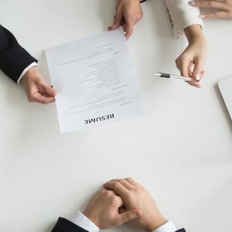Чтение соискателей резюме на собеседовании, вид сверху крупным планом