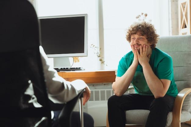 Молодой человек сидит в офисе во время собеседования с работницей, начальником или hr-менеджером, разговаривает, думает, выглядит уверенно