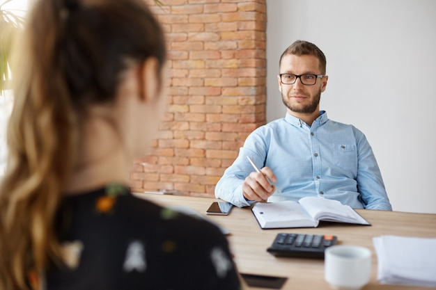 ビジネスコンセプトです。就職の面接。大人のひげを生やした男性hrマネージャーのメガネとシャツの前の職場について質問するブルネットの白人女性の前の軽いオフィスに座っています。