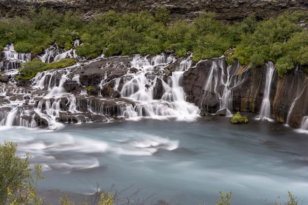 アイスランドの昼間の緑に囲まれたフロインフォッサルの滝