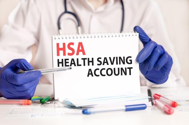 의사의 손에 hsa 카드. 텍스트 hsa와 종이 한 장을 들고 파란색 장갑에 의사의 손