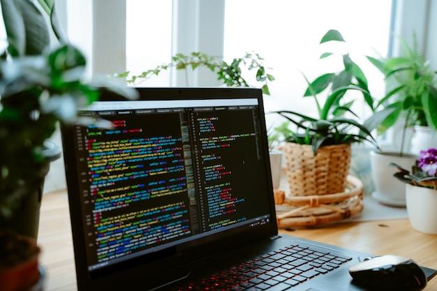 ノートパソコンの画面上のhtmlコード、テーブルの上の家の緑の植物、居心地の良い作業オフィス